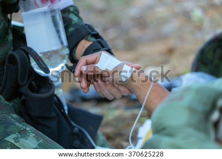 The doctor is giving water to a wounded soldier. - stock photo