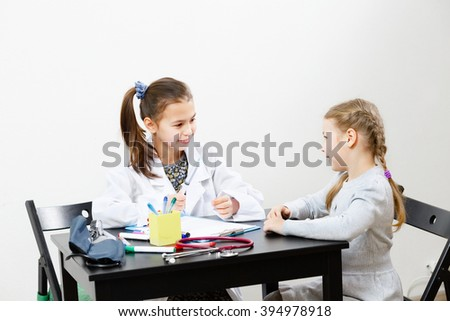 The doctor is receiving a patient, the conversation in the cabinet. girls play - stock photo