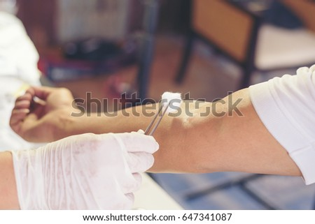 The doctor or nurse  and disinfecting the arm skin by cotton before giving a injection vaccine
