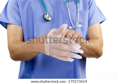 The doctor puts on latex gloves on his hands. - stock photo