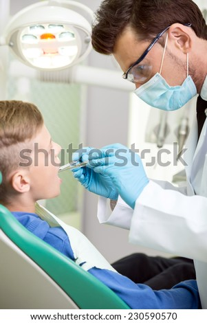The doctor treats a tooth of little boy at dentist's clinic. - stock photo