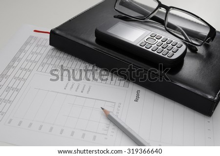 The document of the report on work with a black notebook and glasses on a table of the manager