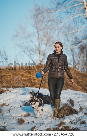 The dog conducts the girl on a trace. - stock photo