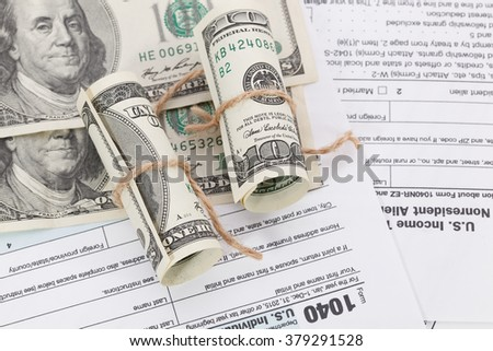 The dollar bills tied with a rope on tax form background