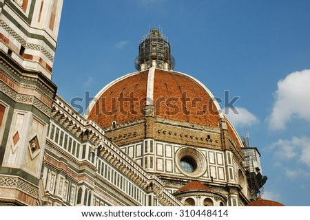 The dome of the Basilica di Santa Maria del Fiore (Basilica of Saint Mary of the Flower) in Florence, Italy on a cloudy blue sky