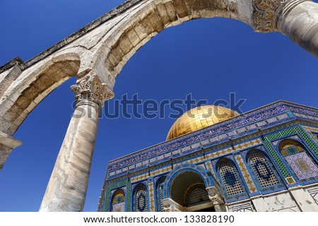 The Dome Of The Rock in the old city of Jerusalem, one of the holiest places to the Islam, from a low and wide angle view through one of the arches leading to it.