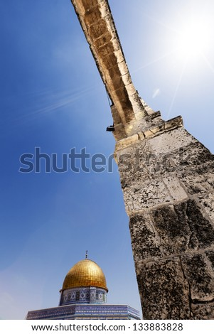 The Dome Of The Rock in the old city of Jerusalem, one of the holiest places to the Islam, from a low and wide angle view through one of the arches leading to it. - stock photo