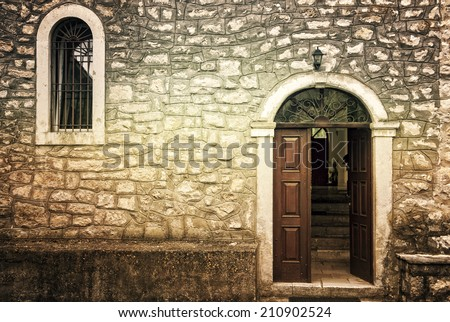 The door and window of an antique stone church on a grungy background - stock photo