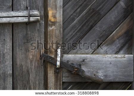 The door bolt closes an old wooden door. Textural wooden background - stock photo