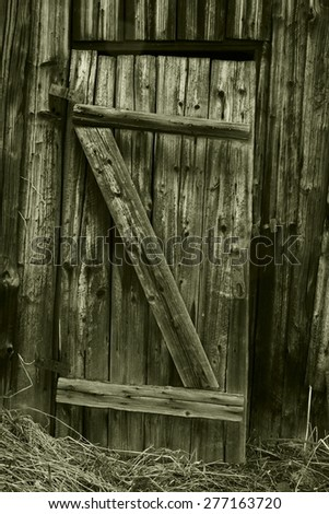 The door to the old rustic barn. - stock photo