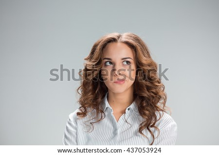 The doubting woman on gray background - stock photo
