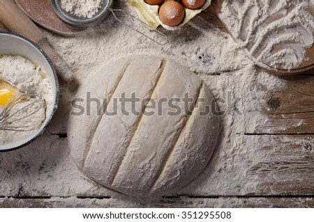 The dough in the form of a loaf of bread on a wooden table in a bakery. Raw loaf of bread. Top view - stock photo