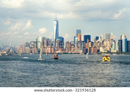 The downtown Manhattan skyline seen from the ocean with boats on the New York Harbor - stock photo