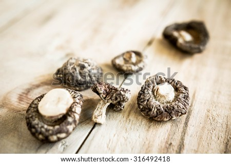 The dried shiitake mushrooms on old wooden table - stock photo