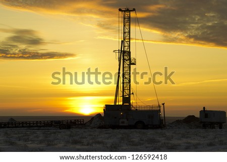 the drilling rig against a sun dawn - stock photo