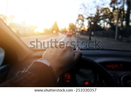The driver goes down the street in sunny day