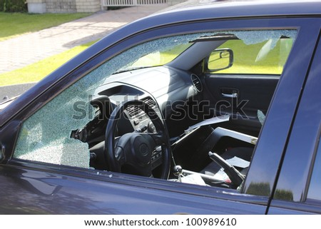 The driver's window has been smashed and the interior vandalized/Auto Theft/A vandalized car in an urban setting - stock photo