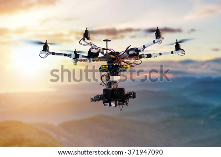 The drone with the professional cinema camera flying over the misty mountains at sunset. Blurred background. - stock photo