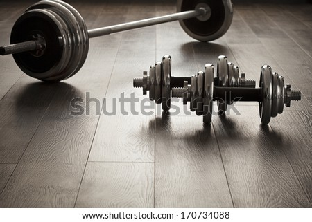 The dumbbells for fitness on wooden floor with empty space - stock photo