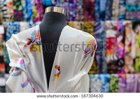 The dummy dressed in a dress from white fabric with a flower pattern, tied with a tape with a bow. - stock photo