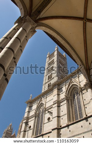 The Duomo di Siena (Siena cathedral) under a blue sky in the summer.