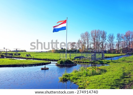 The dutch national flag in a typical dutch landscape - stock photo