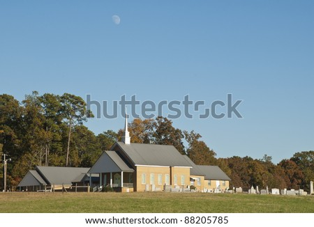 The early moon rises over a church and graveyard in the South Carolina Uplands.