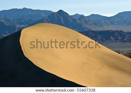 The early morning light hits the ridge line and peak of a sand dune in Mesquite Flat, Death Valley National Park, California. - stock photo