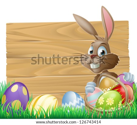 The Easter bunny with a basket of Easter eggs with more Easter eggs around him by a wood sign board - stock photo