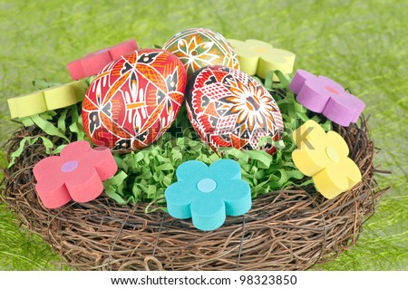 The easter painted eggs in nest and flowers.