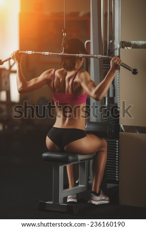 The effect of oil paints. Body of a beautiful young girl in the fitness room rear view. Athletic young woman doing a fitness workout - stock photo