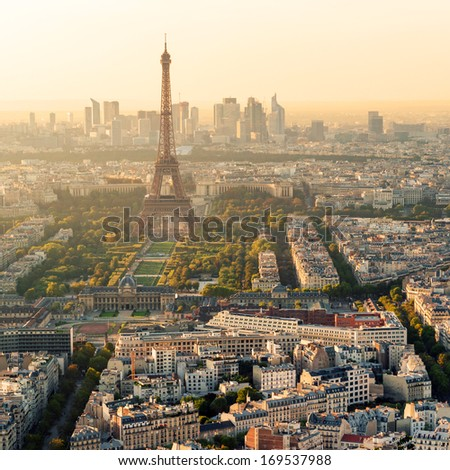 The Eiffel tower at sunset in Paris. La Defense in the background