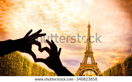 The Eiffel Tower in Paris and hands in a heart shape - stock photo