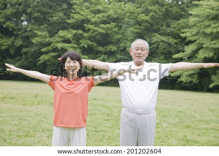 The elderly couple working out while listen to the radio in the park - stock photo