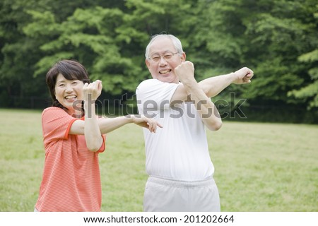 The elderly couple working out while listen to the radio in the park