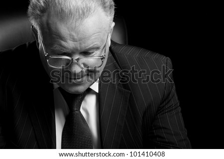 The elderly man in eyeglases reads the document. A photo monochrome - stock photo