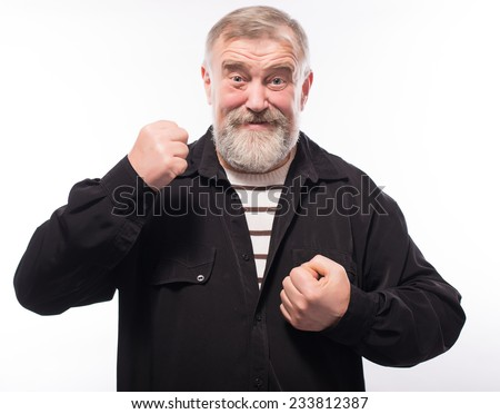 The elderly man threatens with a fist