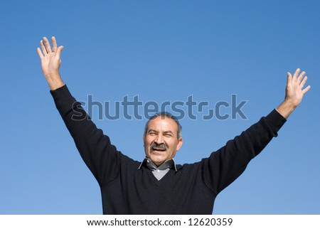 The elderly man with  lifted hands against the sky - stock photo