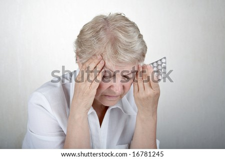 The elderly woman holds hands a head, going to accept tablets