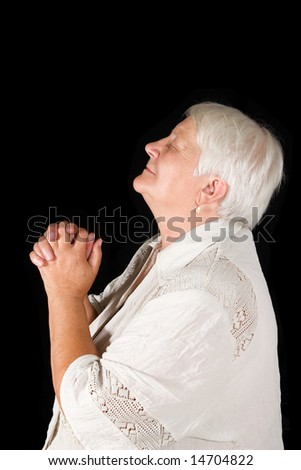 The elderly woman prays on a black background