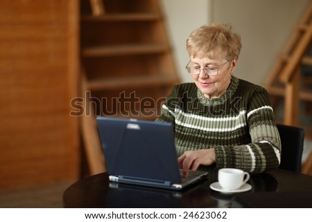 The elderly woman writes  on the computer - stock photo