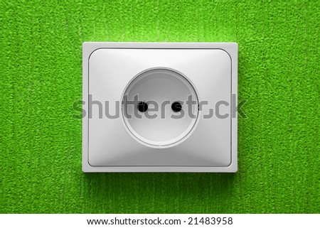 The electric socket in a green wall