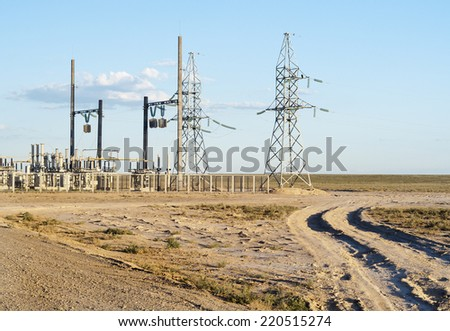 The electric transformer towers in the steppe - stock photo