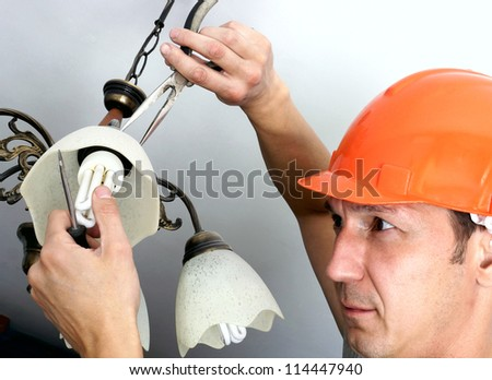 the electrical worker repairs a lighting chandelier - stock photo