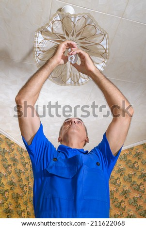 The electrician replaces a bulb in a chandelier - stock photo