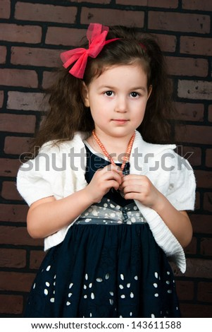 the elegant girl with wavy hair against a brick wall