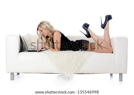 The elegant woman on a white sofa with the laptop. Business concept. - stock photo