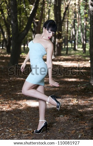 The emotional sexual brunette in a short dress in park