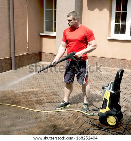 The employee is engaged in athletic cleaning the home on a sunny day