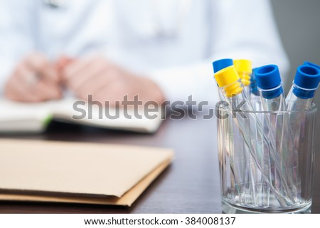 The empty test tubes in glass standing on the desk in doctors office  / empty test tube